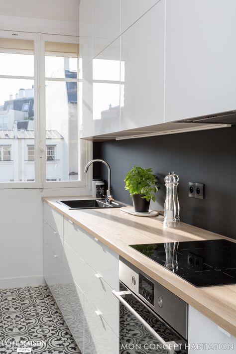 kitchen with pattern floor, white cabinet with wooden top, white cabinet on top, black wall, windows, white wall