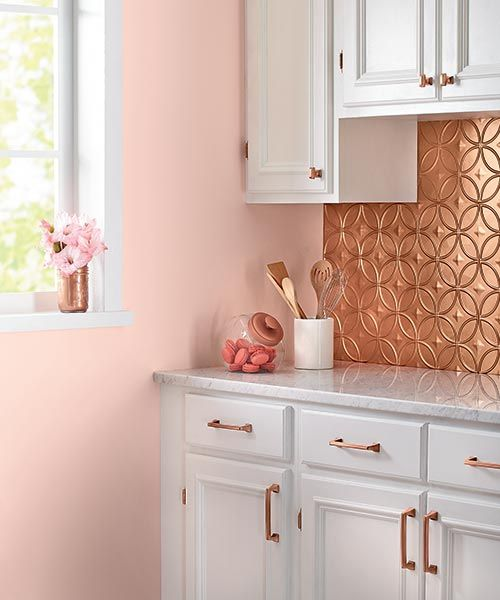 kitchen with white cabinet, pink painted wall, white sounter top, rose gold backsplash