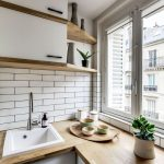 Kitchen With White Cabinet Under Wooden Countertop, White Sink, White Floating Cabinet With Shelves, Near The Window, White Subway Backsplash