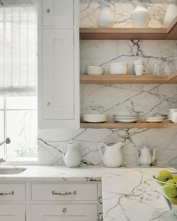 kitchen with white cabinet with white marble counter top, white cabinet on top with wooden shelves, marble on the wall