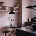 Kitchen With White Floor, Black Cabinet With Metalic Counter Top, Pink Wall, Pink Shelves, White Tiles On Wall, Round Dining Table With Chair And Stool, Black Pendant