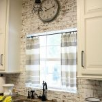 Kitchen With White Open Brick Wall, White Cabinet, Brown Kitchen Top, Windows, Silver Sink With Black Faucet