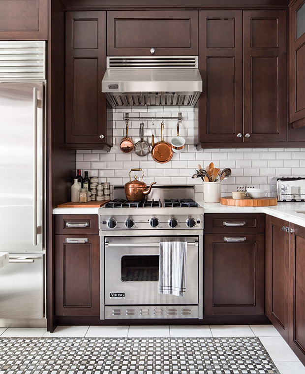 kitchen with white tiles on floor, brown cabinet at the bottom and top of white kitchen top, silver stove and oven, silver fridge