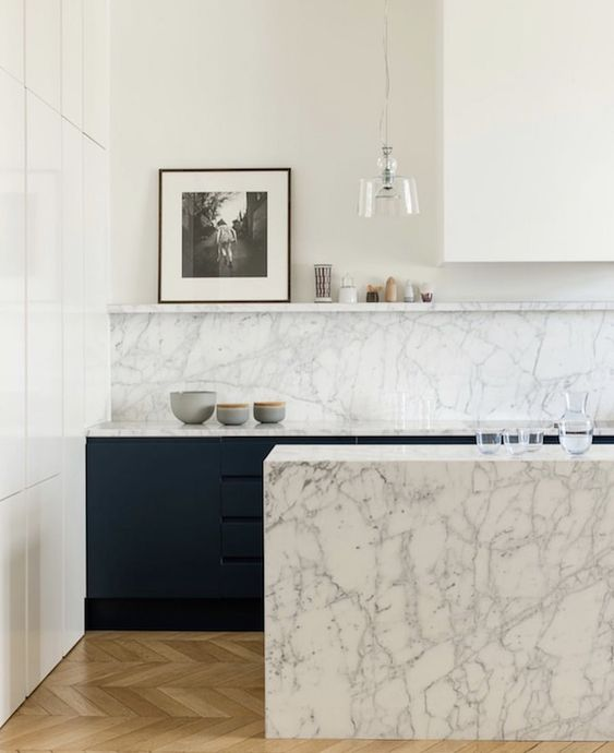 kitchen with white wall, white cabinet on top, green cabinet under the white marble top, white marble backsplash, white marble island