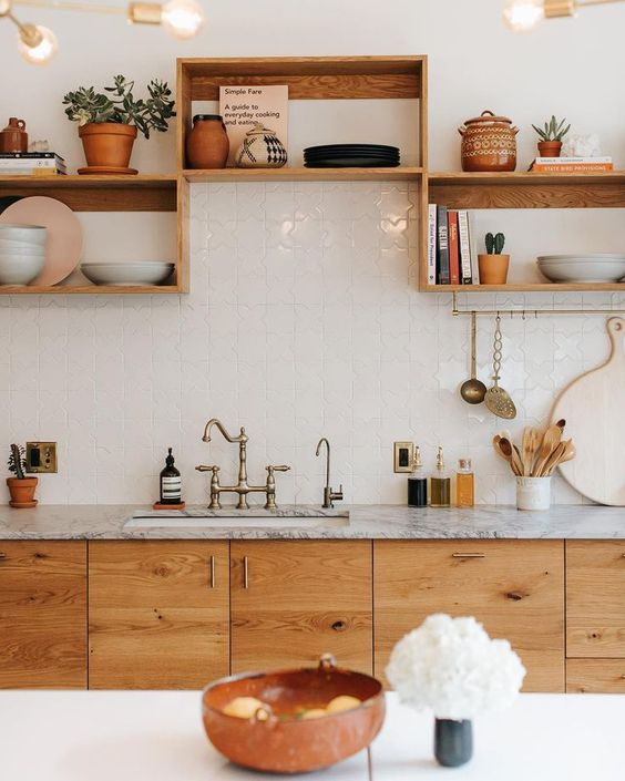 kitchen with wooden cabinet under grey marble countertop, white top island, wooden shelves on the wall, white tiles on the wall