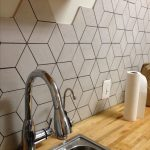 Kitchen With Wooden Counter Top, Grey Geometric Tiles On Backsplash, Silver Sink And Faucet