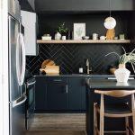Kitchen With Wooden Floor, Black Island With Wooden Chairs, Black Cabinet, Black Herringbone Backsplash, Wooden Open Shelves