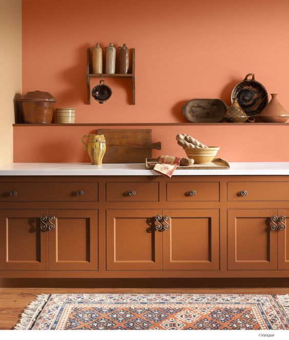 kitchen with wooden floor, rug, warm orange cabinet, orange wall, white counter top, wooden shelves