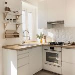 Kitchen With Wooden Floor, White Cabinet Under Wooden Counter Top, White Cabinet On Top, White Floating Shelves, White Hecagon Tiles, White Wall, Window