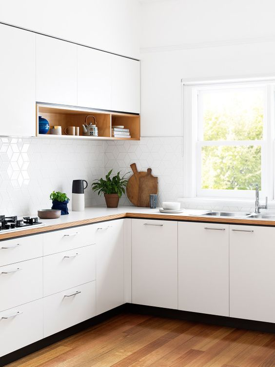 kitchen with wooden floor, white cabinet uner white wooden counter top, white hexagon tiles backsplash, white floating cabinet with shelves, window