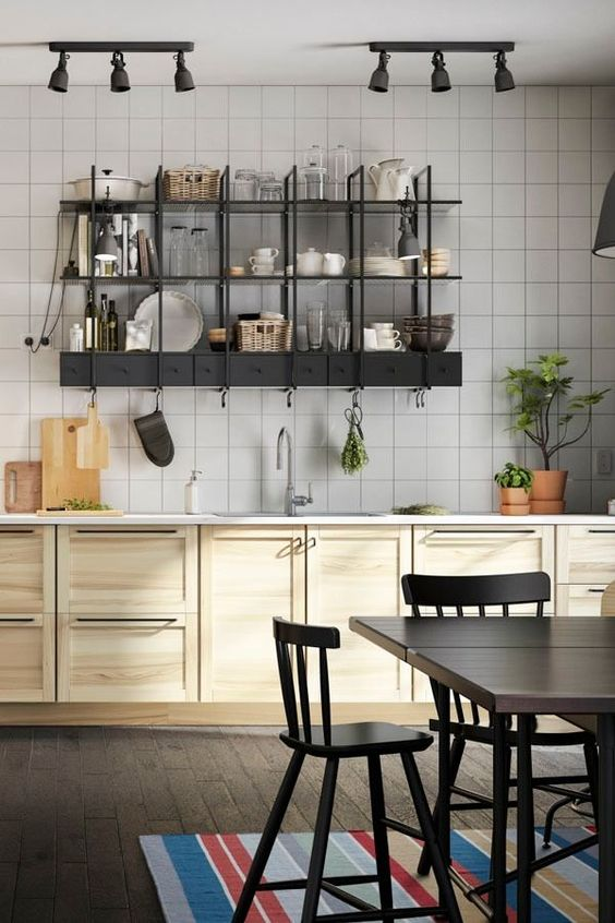 kitchen with wooden floor, white tiles wall, wooden cabinet with white countertop, black metal shelves