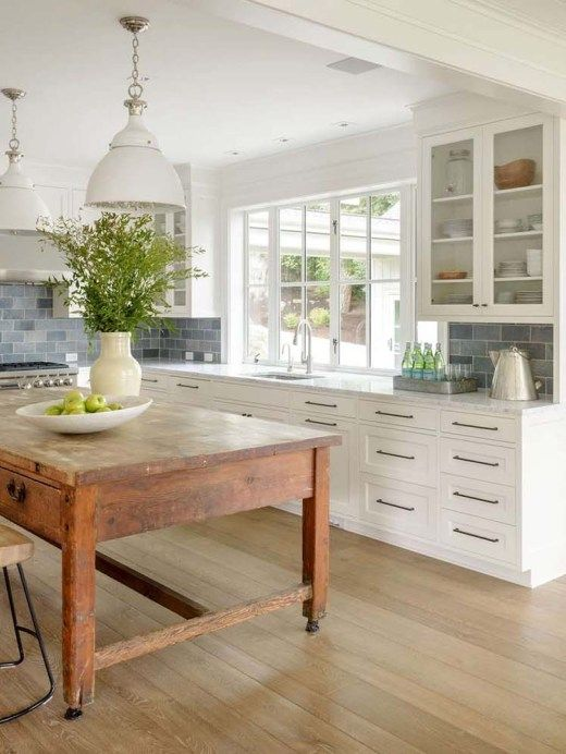 kitchen with wooden floor, white wooden cabinet, glass cabinet on top, large glass windows, white pendant, big wooden table in the middle