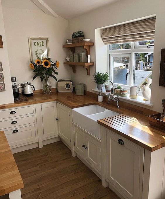 kitchen with wooden floor, white wooden cabinet with brown wooden top, white ceramic sink, silver faucet, windows with shade