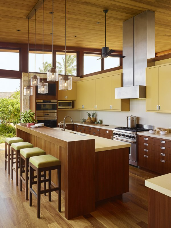 kitchen with wooden floor, wooden cabinet at the bottom, yellow cabinet on top of the white counter top, long wooden island with lime stools, fan, pendants