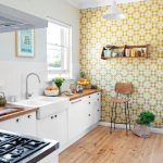 Kitchen With Wooden Floor, Yellow Accent Wall, White Wall, White Cabinet Under Wooden Kitchen Top, White Sink, Windows, White Pendant