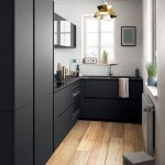 Kitchen With Wooden Planks Floor, White Wall, Smooth Black Cabinet And Cupboards, Black Counter Top