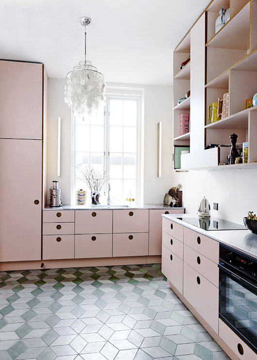 ktichen with hexagon tiles with cube effect, white wall, pink cabinet and cupboards, pink shelves, white chandelier
