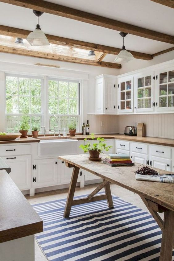 large kitchen with white cabinet under wooden kitchen top, white cabinet with glass door on top, long wooden table in the middle