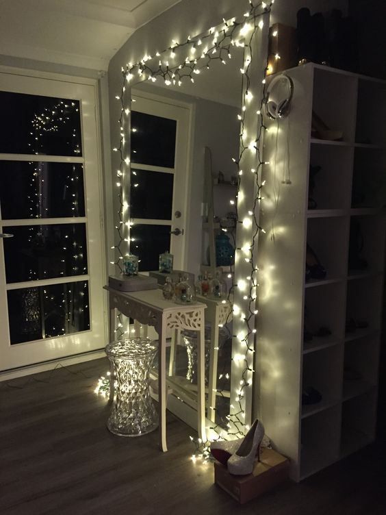 large white mirror with fairy lights around the frame