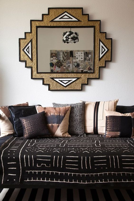 living room, black white stripes rug, black sofa bed with tribal pattern, white wall, wall mirror