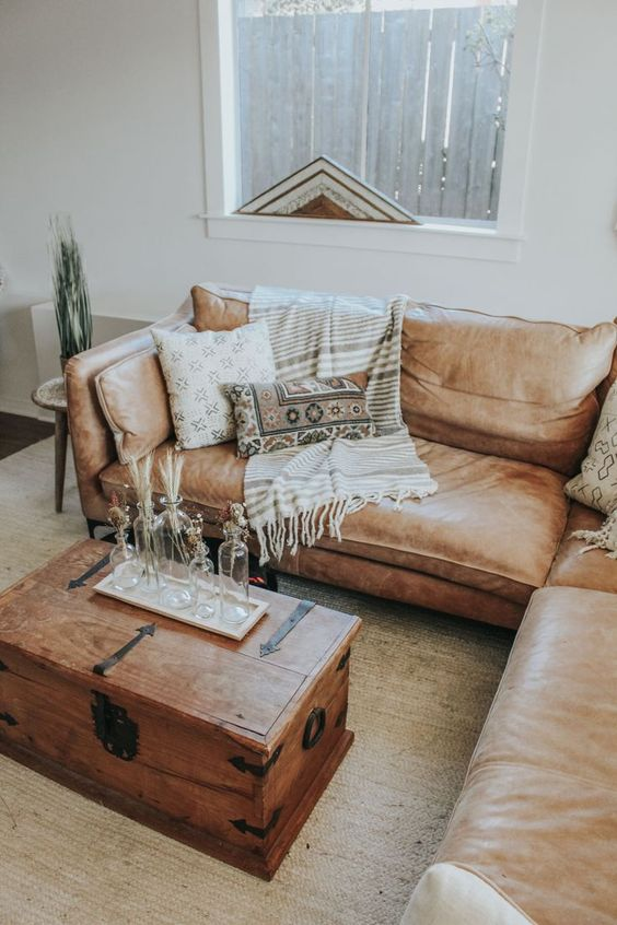 living room, brown rug, wooden chest as coffee table, brown leather corner sofa, white wall