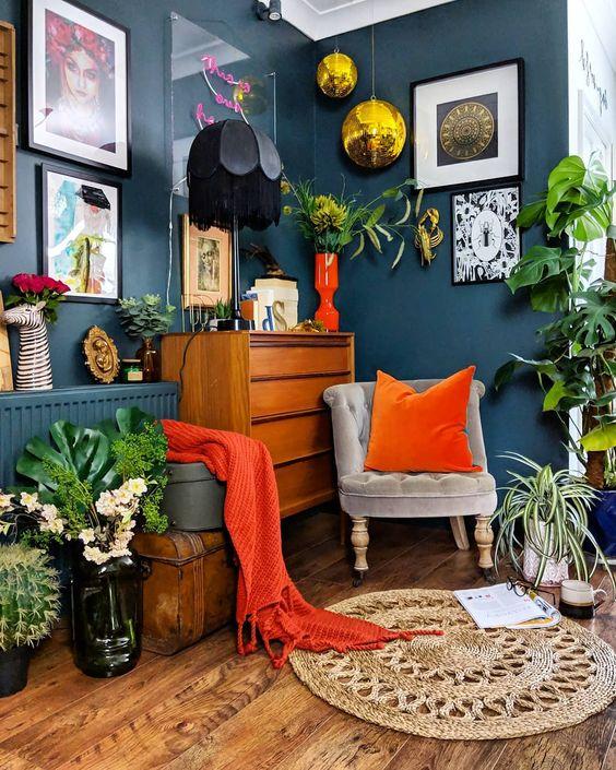 living room corner with grey wall, wooden floor, grey chair, wooden cabinet, shelves, black table lamp, plants, golden ceiling accessory, rattan rug