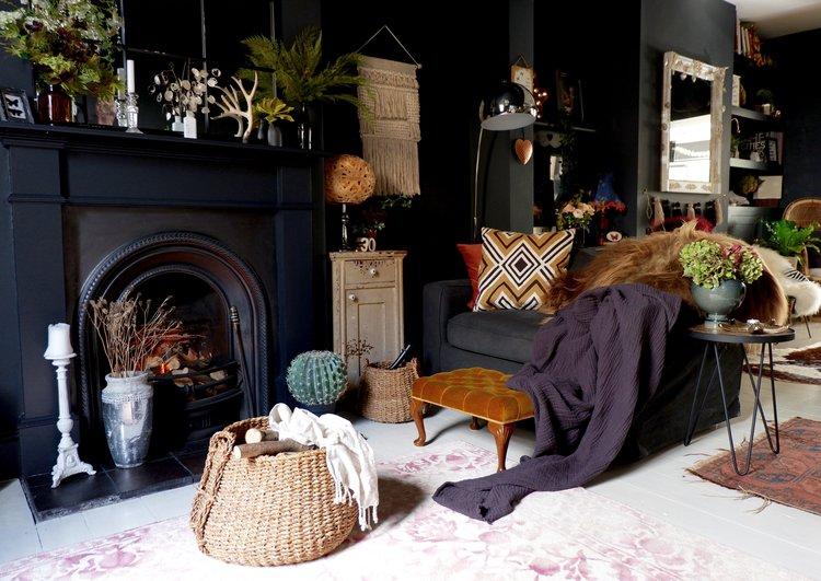 living room rug, black chair, black walls, black fireplace, woven basket, macrame, silver floor lamp, orange ottoman
