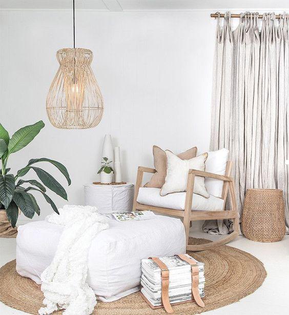 living room, white floor, rattan rug, wooden rocking chair, white square ottoman, rattan covered pendant