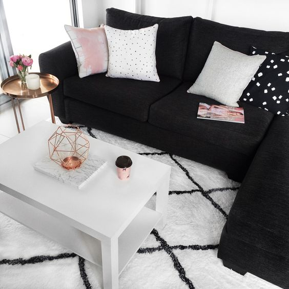 living room white floor, white rug, white wooden simple coffee table, black sofa, golden side table, white wall