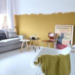 Living Room, White Wooden Floor, Grey Sofa, White Rocking Chair, White Wall, Half Yellow Wall, Wooden Round Modern Coffee Table