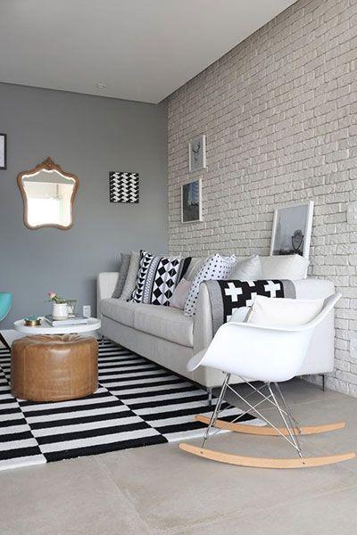 living room with grey flooring, black white rug, brown round ottman, white round coffee table, white sofa, white rocking chair, grey wall, white painted open brick