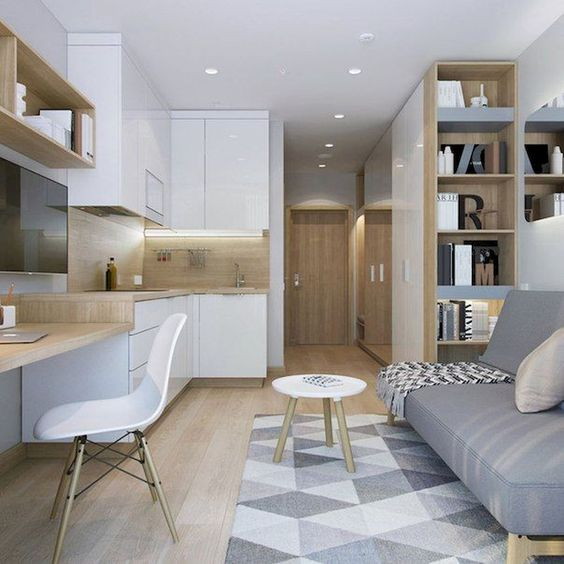 living room with grey sofa, grey rug, wooden table with white chair, white cabinet on kitchen, shelevs on side