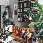 Living Room With Grey Wall, Brown Wooden Floor, Grey Rug, Brown Leather Sofa, Wooden Coffee Table, Wall Hung Wooden Book Shelves, Plants