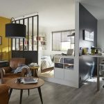 Living Room With Grey Wooden Floor, Round Coffee Tbale, Brown Leather Chair, Open Bedroom With Half Partition, Shelves, Floating Dining Table
