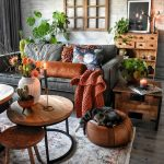 Living Room With Grey Wooden Floor, Rug, Ottoman, Coffee Table, Side Table, Sofa, Wooden Shelves, Faux Window, Plants On The Table