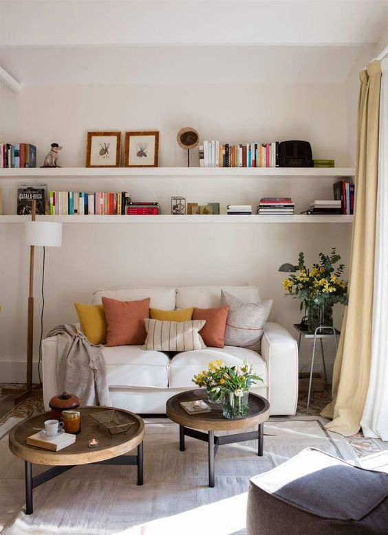 living room with rug floor, white sofa, two round coffee tables, white shelves on top, white covered floor lamp