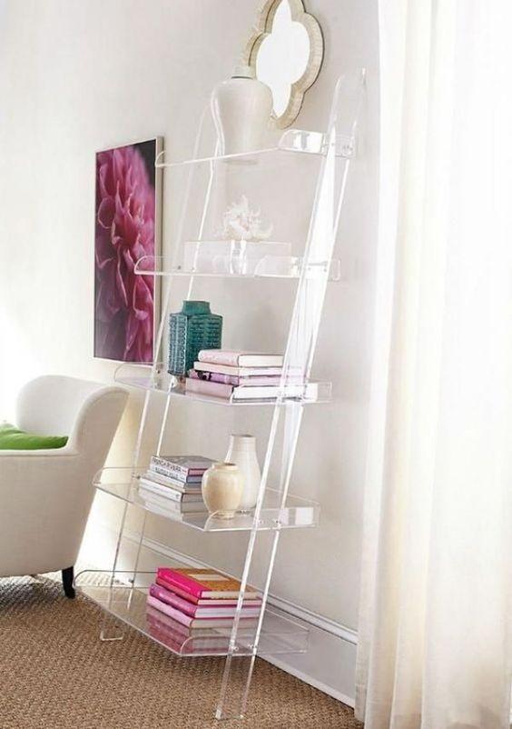 living room with rug flooring, white chair, acrylic bookshelves