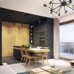 Living Room With White Floor, Rug, White Ottoman, Wooden Blocks Coffee Table, Grey Sofa, Small Black Kitchen, Wooden Dining Table From The Island, TV