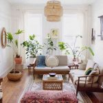 Living Room With White Wall, Wooden Floor, Wooden Bench With White Cushion, Plants, Rattan Lamp, Coffee Table, Red Square Ottoman