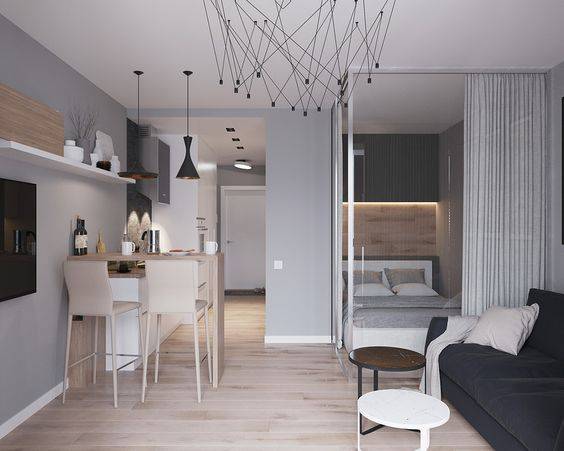 living room with wooden floor, dark grey sofa, round coffee tables, high wooden tables for dining with wooden stools, bedroom with curtain