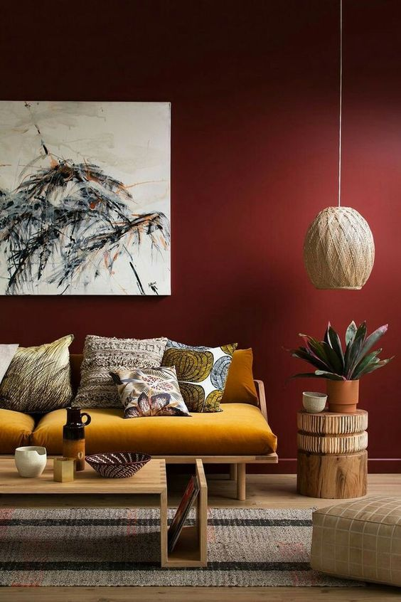 living room with wooden floor, rug, wooden bench with mustar cushion, wooden coffee table, ottoman, maroon wall, roud side table, pendant