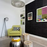 Living Room With Wooden Floor, Rug, Wooden Coffee Table, Green Chair, Black Textured Accent Wall, Painting