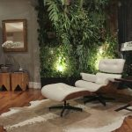 Living Room With Wooden Floor, White Lounge Chair, Wooden Sde Tables, Grey Wall, Plants On The Wall, Lamps On The Plants