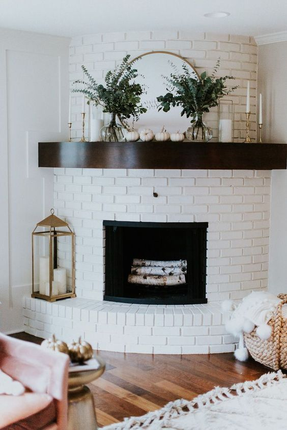 living room with wooden floor, white rug, chair, side table, curvy wall for fireplace with open brick painted in white