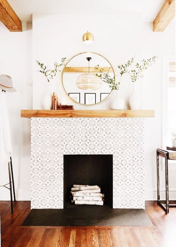living room with wooden floor, white wall, white pattern fireplace with wooden shelves on top, round mirror, wooden beams on ceiling