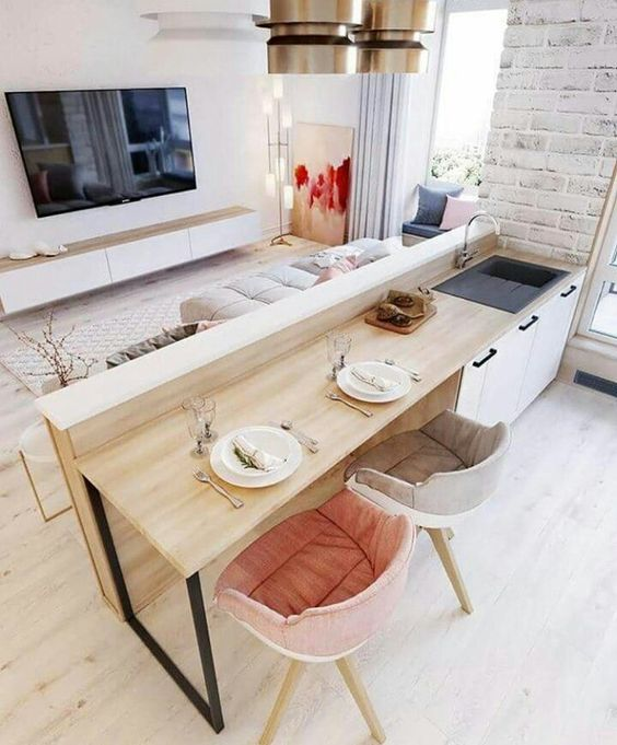 living room with wooden floor, wooden cabinet with white door, rug, beige sofa, wooden table from the countertop, sink, wooden chairs