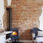 Living Room With Wooden Look Floor, White Wall With Exposed Brick Wall, Fire Furnace In Black, White Cabinet