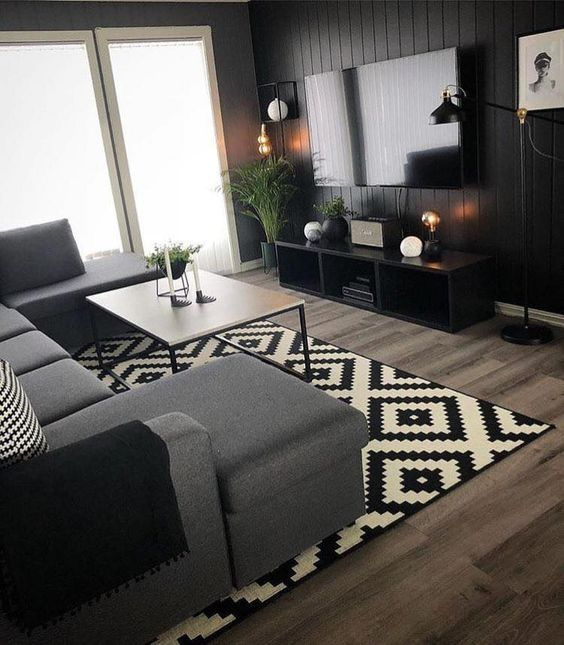living room wooden floor, black white rug, black accent wall, grey sofa, white coffee table