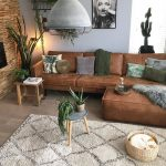 Living Room, Wooden Floor, Rug, Brown Sofa, Round Coffee Table, Wooden Stool, Basket, White Color, Brown Textured Wall
