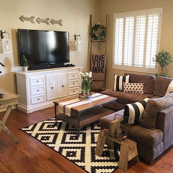 living room, wooden floor, rug, brown sofa, wooden coffee table, white cabinet, TV, wooden rack, soft yellow wall